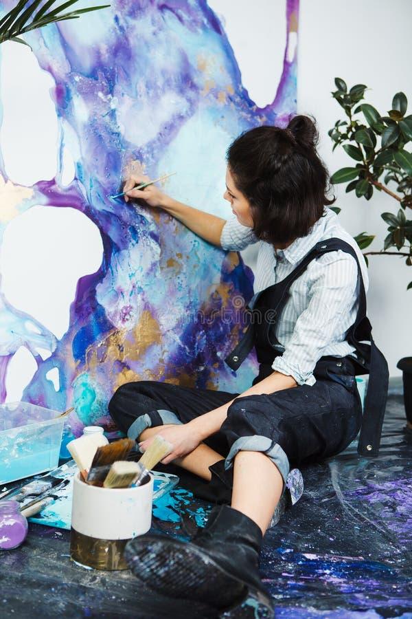 La muchacha mezcla las pinturas en la paleta, yendo a comenzar terapia de los artes foto de archivo