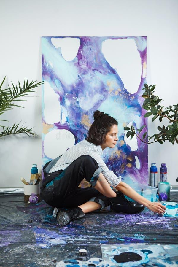 La muchacha mezcla las pinturas en la paleta, yendo a comenzar terapia de los artes fotografía de archivo