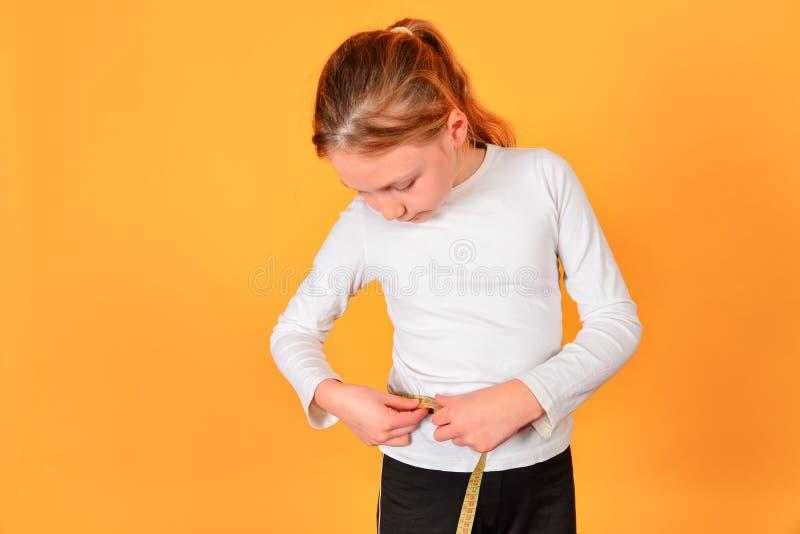 La muchacha mide la cintura por centímetro, en un fondo amarillo en el estudio imagenes de archivo