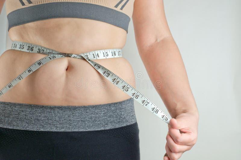 La muchacha mide el vientre graso imagenes de archivo
