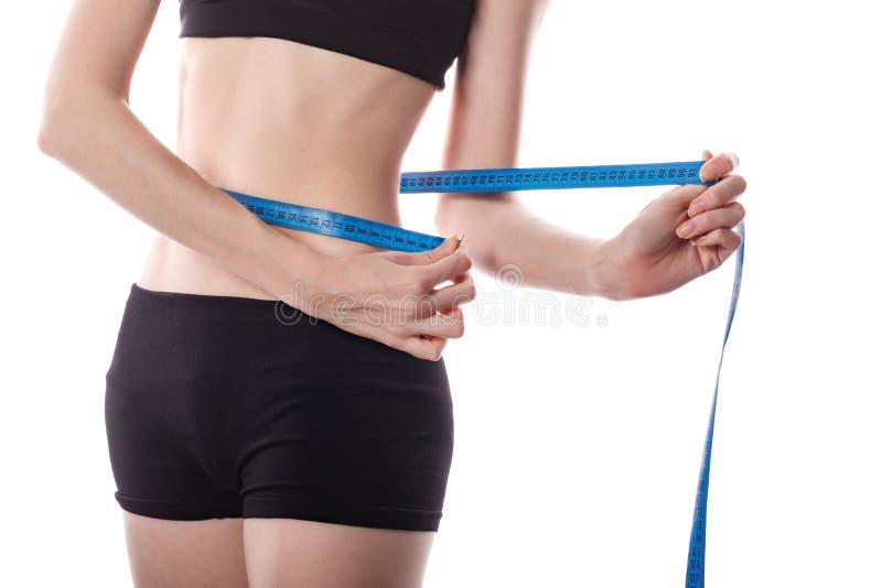 La muchacha mide la pérdida de peso de la cintura imagenes de archivo