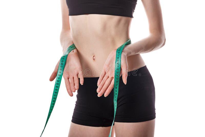 La muchacha mide la pérdida de peso de la cintura imagen de archivo