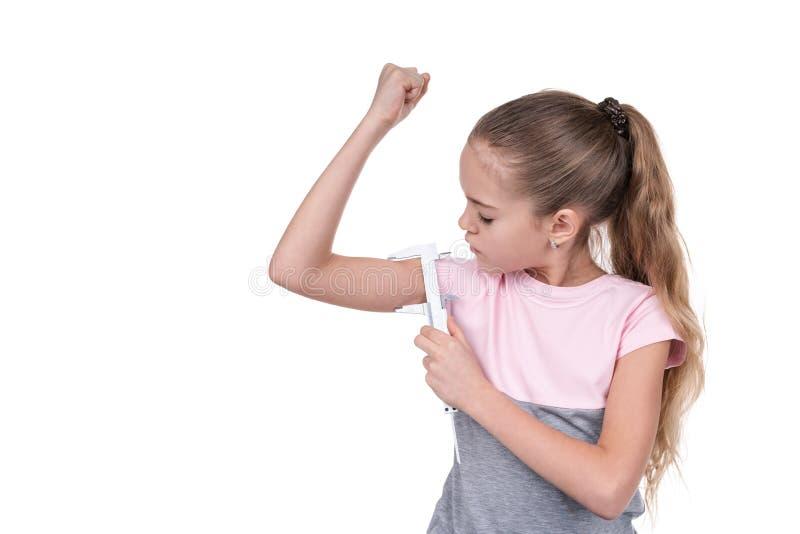 La muchacha mide los músculos con un calibrador fotografía de archivo