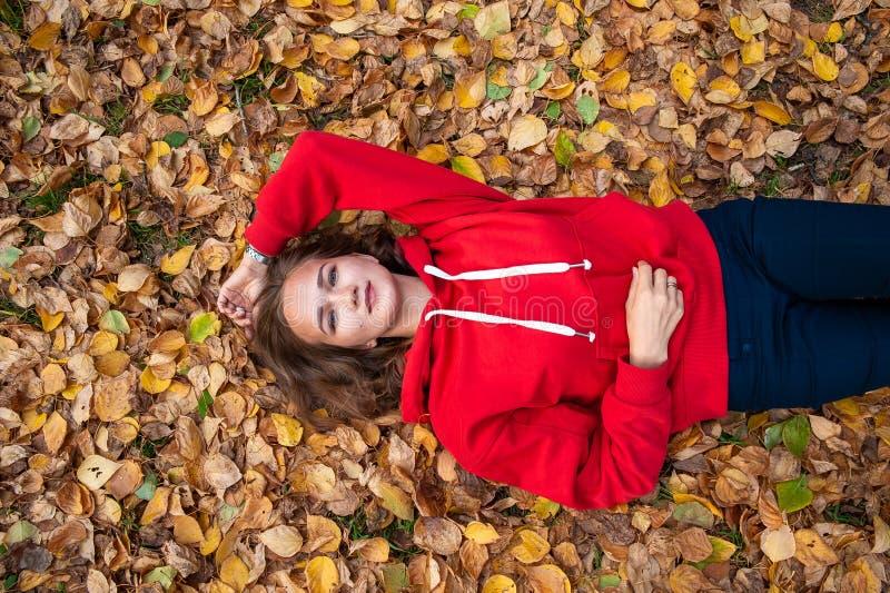La muchacha miente en el follaje del otoño foto de archivo