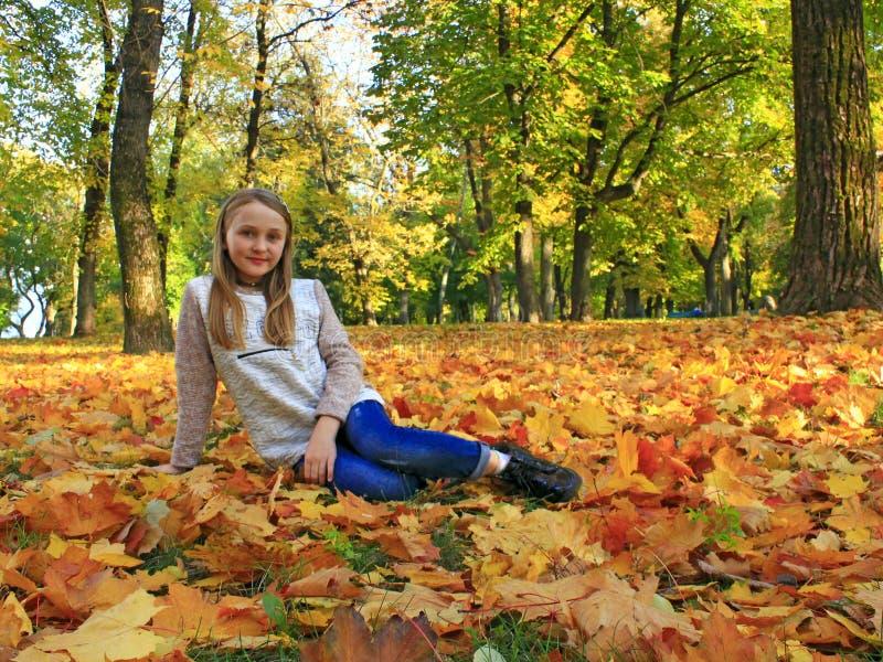 La muchacha miente en las hojas amarillas en parque del otoño fotos de archivo libres de regalías