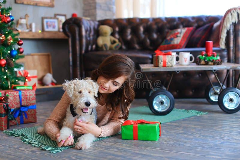 La muchacha miente en piso en la tela escocesa que abraza el perro, sonriendo y presentando para fotos de archivo libres de regalías