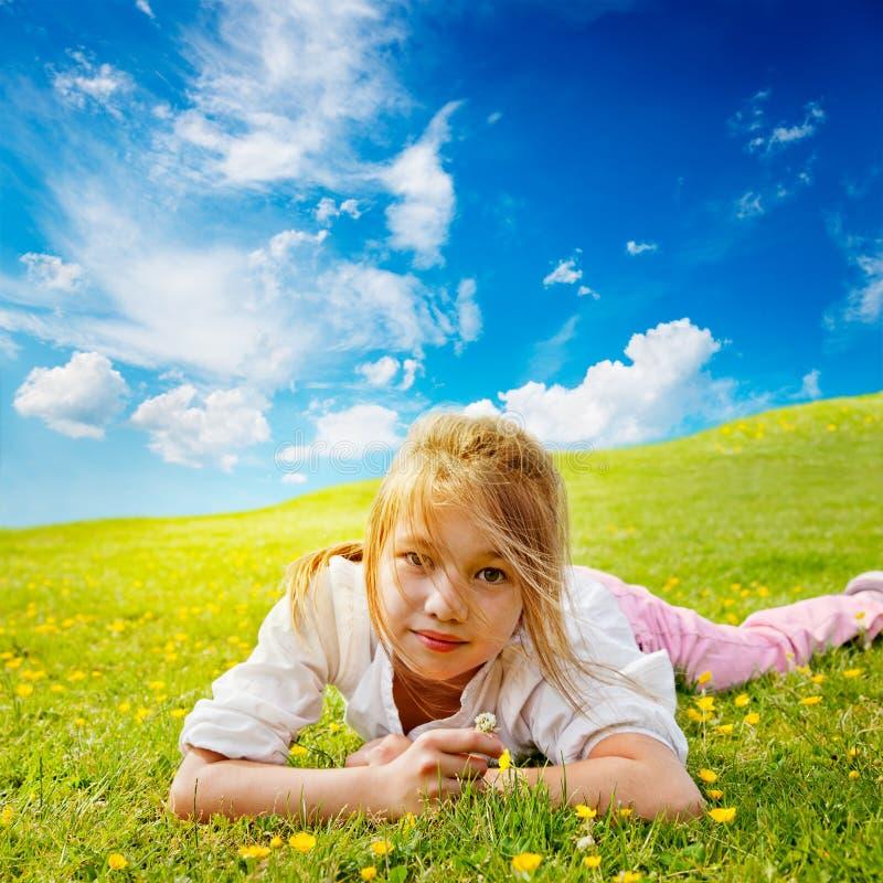 La muchacha miente en prado asoleado fotos de archivo