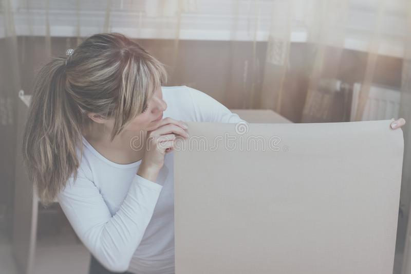La muchacha mira abajo mientras que se coloca con una hoja de papel o elige el papel pintado foto de archivo