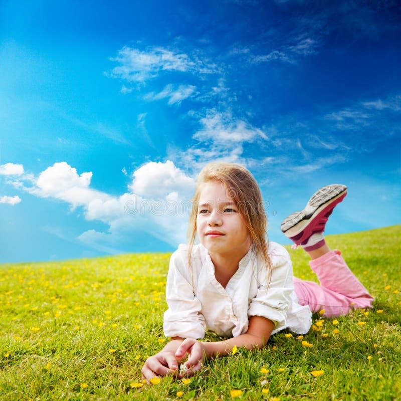 La muchacha mira alrededor de prado asoleado fotos de archivo