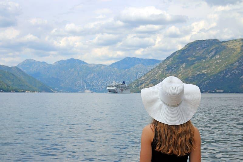 La muchacha mira el barco de cruceros que entra en la bahía de Kotor fotos de archivo libres de regalías