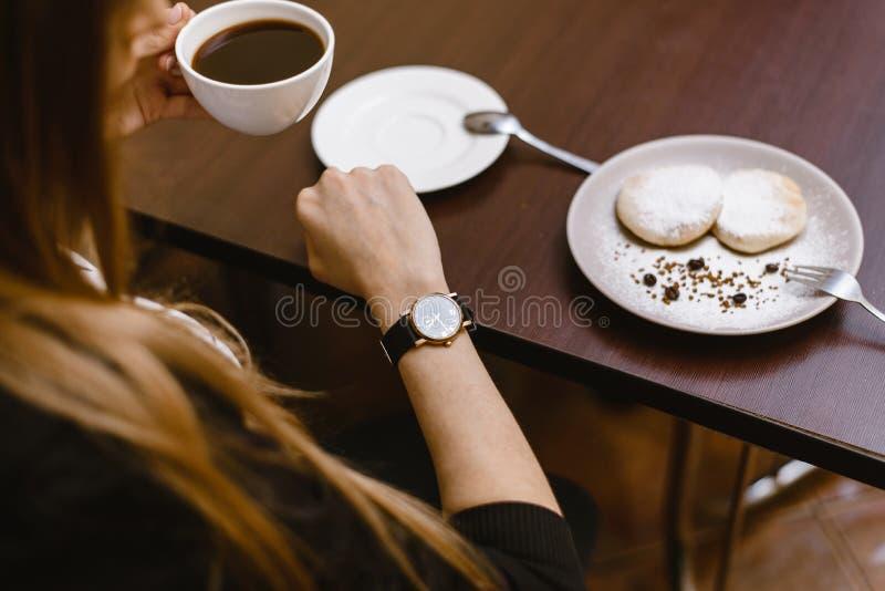 La muchacha mira el reloj en un café sobre una taza de café tiempo en el reloj - la época para el desayuno, postre imagen de archivo