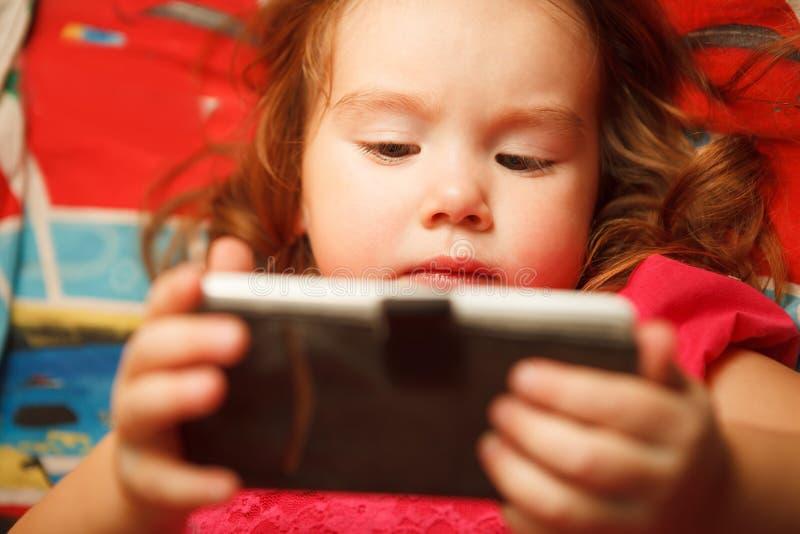 La muchacha mira el teléfono de cerca los peligros de los artilugios para la visión del ` s de los niños fotos de archivo libres de regalías