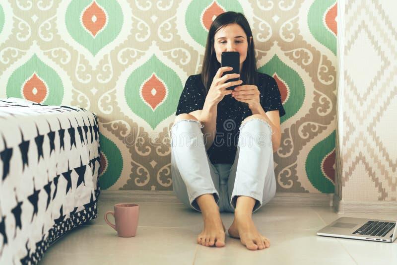 La muchacha mira en el tel?fono fotografía de archivo libre de regalías