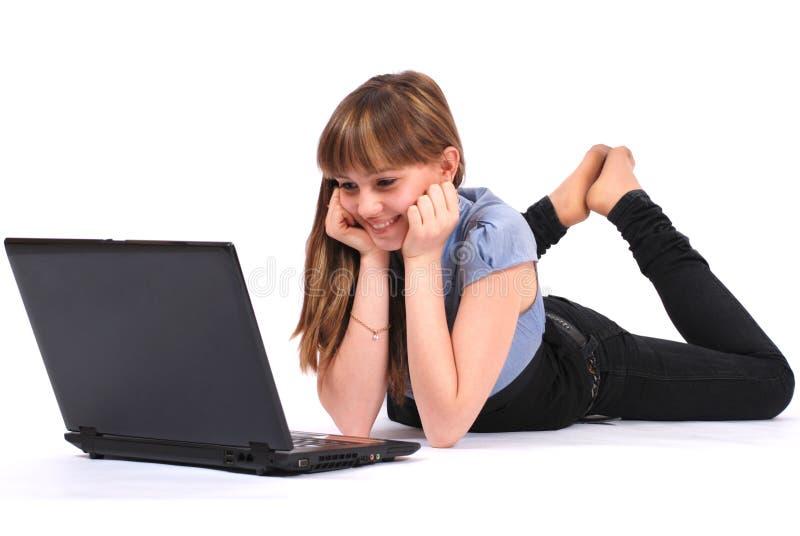 La muchacha mira en la computadora portátil imagen de archivo libre de regalías