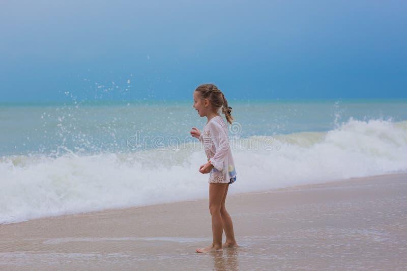 La muchacha mira en la distancia el océano en la playa en rabiar de la tormenta foto de archivo libre de regalías