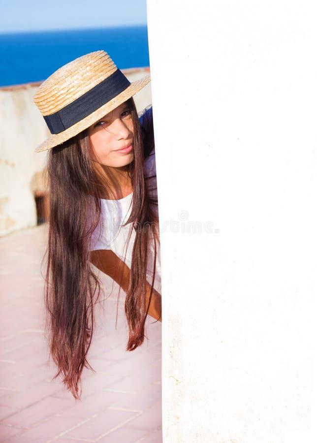 La muchacha mira a escondidas hacia fuera de detrás la pared imagen de archivo libre de regalías