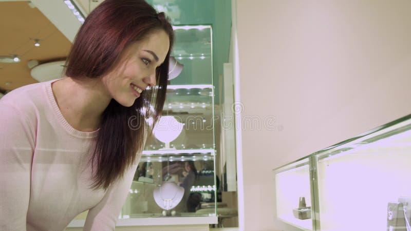La muchacha mira la exhibición de las compras con joyería fotos de archivo libres de regalías