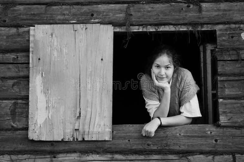 La muchacha mira hacia fuera la ventana foto de archivo
