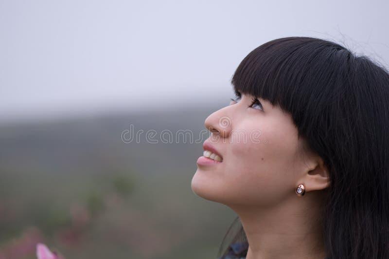 La muchacha mira para arriba al cielo imagen de archivo libre de regalías