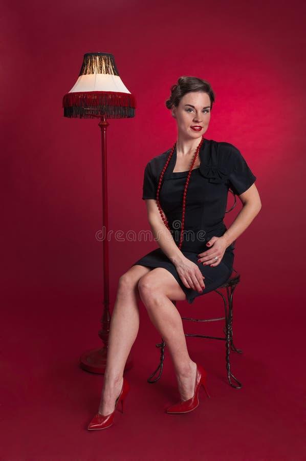 La muchacha modela en vestido negro se sienta con la lámpara franjada imagen de archivo