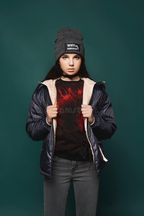 La muchacha modelo adolescente morena joven, en chaqueta y sombrero, se coloca sobre fondo verde oscuro, imagenes de archivo