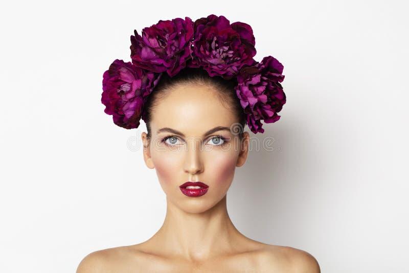 La muchacha modelo atractiva de la belleza con las flores de la peonía enrruella Piel de moda del balneario del maquillaje de la  imagenes de archivo
