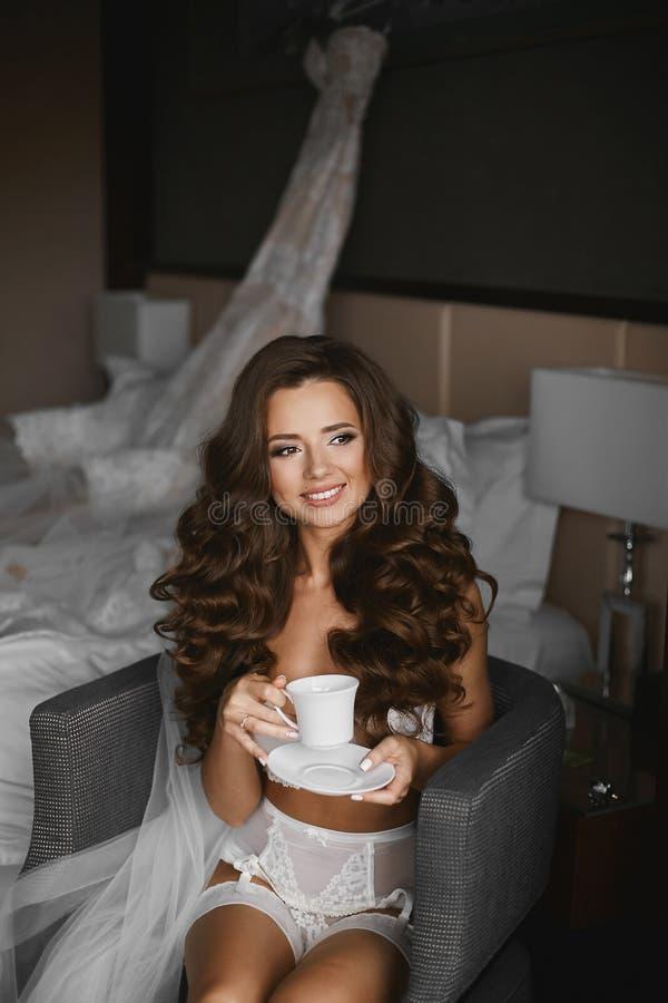 La muchacha modelo morena atractiva y joven en ropa interior y las medias, con la taza de café, está presentando en la butaca - m fotografía de archivo