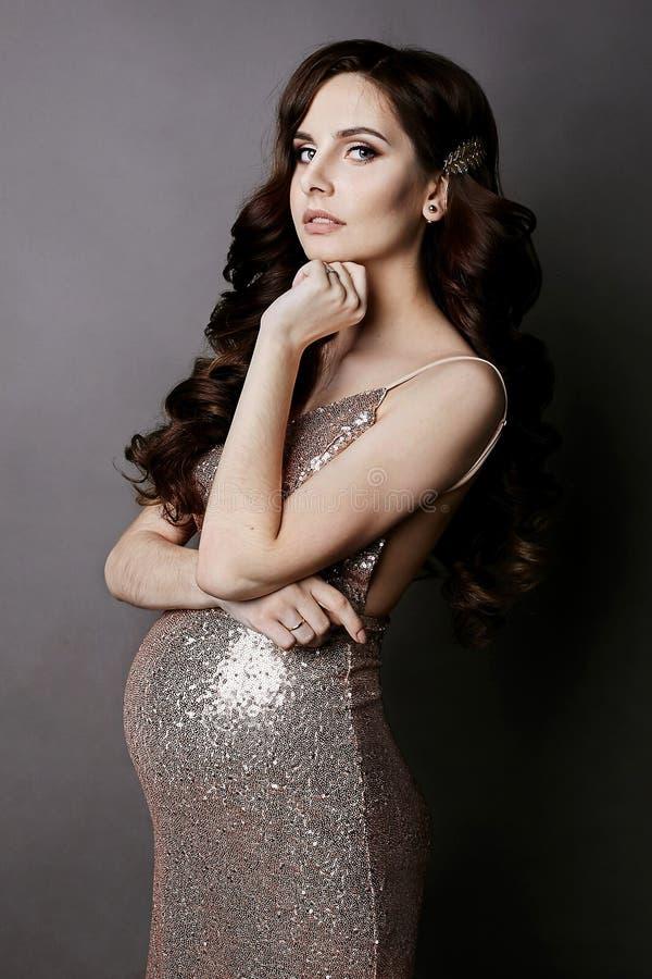 La muchacha modelo morena de moda y embarazada con maquillaje apacible, en el vestido con las lentejuelas del oro, mira la cámara imágenes de archivo libres de regalías