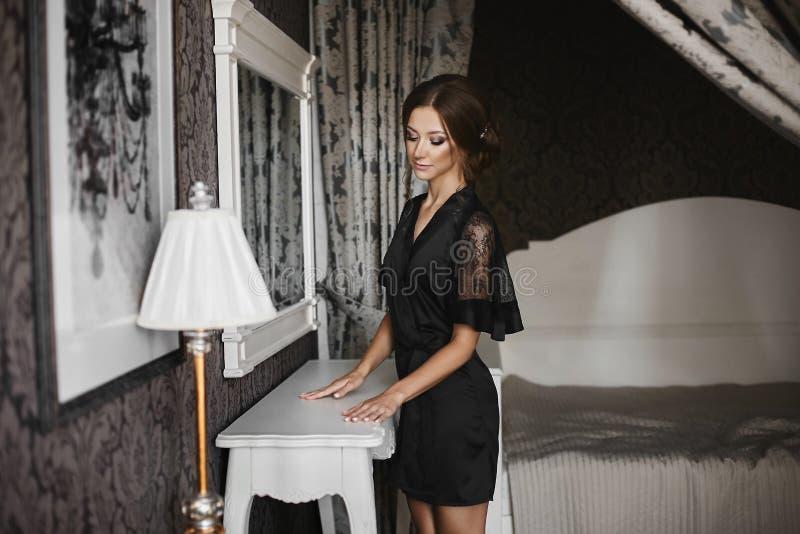 La muchacha modelo morena hermosa, atractiva y de moda con maquillaje brillante en bata negra corta del satén mira abajo y presen imagen de archivo