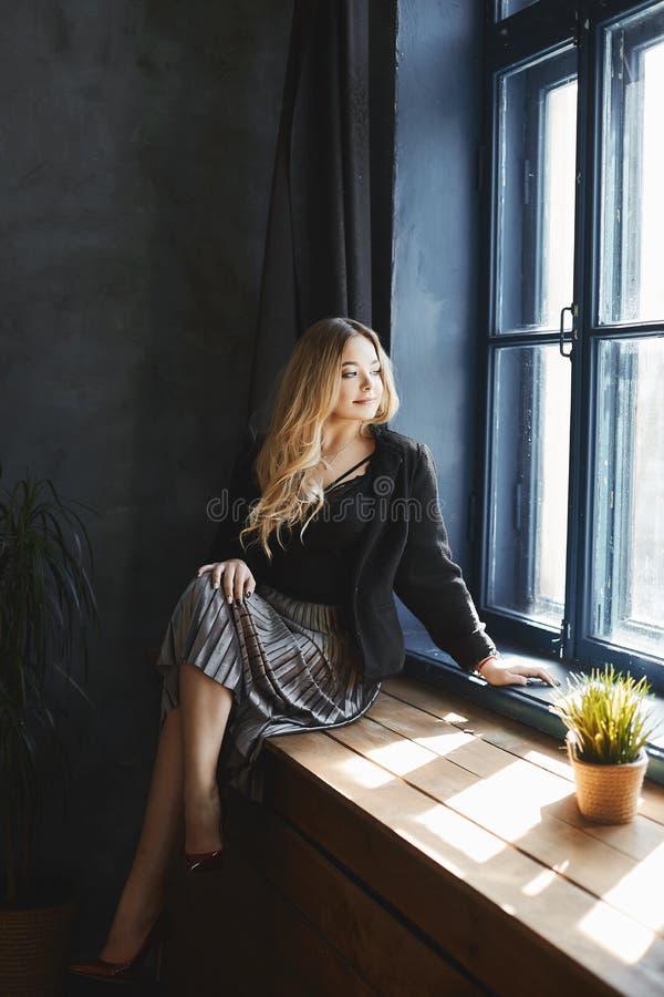 La muchacha modelo rubia hermosa y de moda con el pecho grande en la falda de plata y en blusa negra del satén se sienta en el wi imágenes de archivo libres de regalías