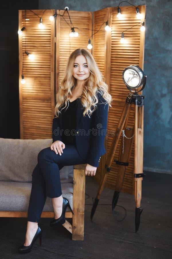 La muchacha modelo rubia hermosa y de moda con los ojos azules en traje azul marino elegante se sienta en un sofá, sonriendo y pr imagen de archivo libre de regalías
