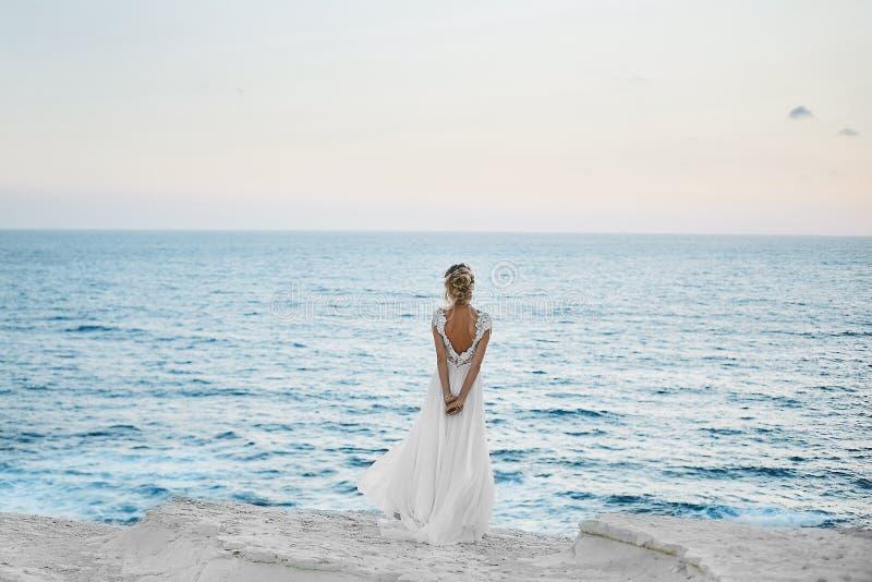 La muchacha modelo rubia joven hermosa en el vestido blanco retrocede y mira el mar fotografía de archivo