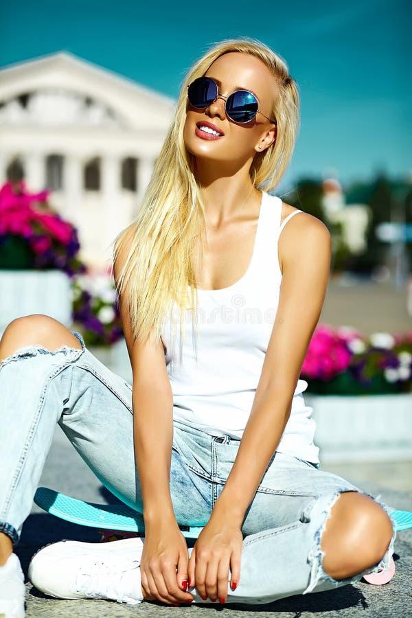 La muchacha modelo rubia joven hermosa en inconformista del verano viste con el monopatín fotos de archivo