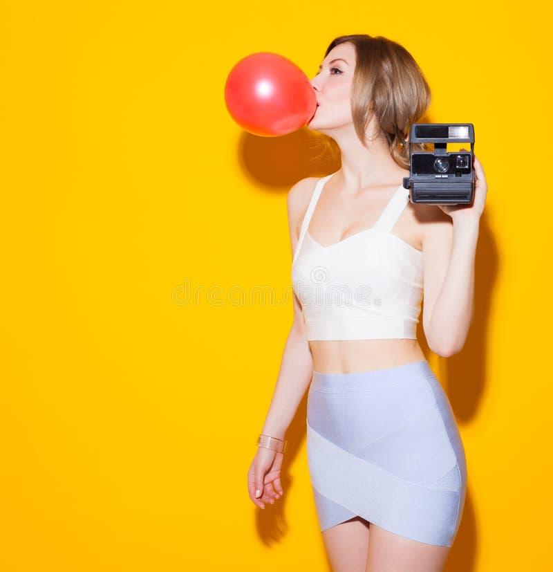 La muchacha moderna de moda que presenta en top y falda coloridos infla la burbuja roja del chicle y con una cámara del vintage e imagenes de archivo