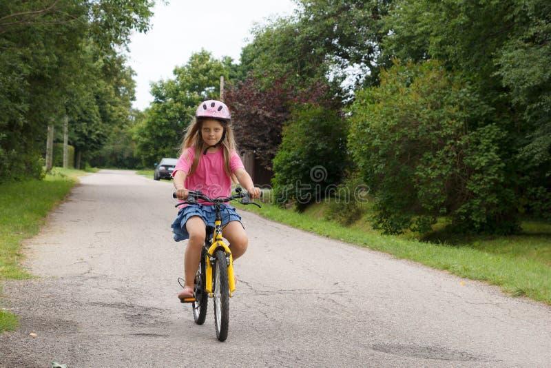 La muchacha monta una bicicleta foto de archivo libre de regalías