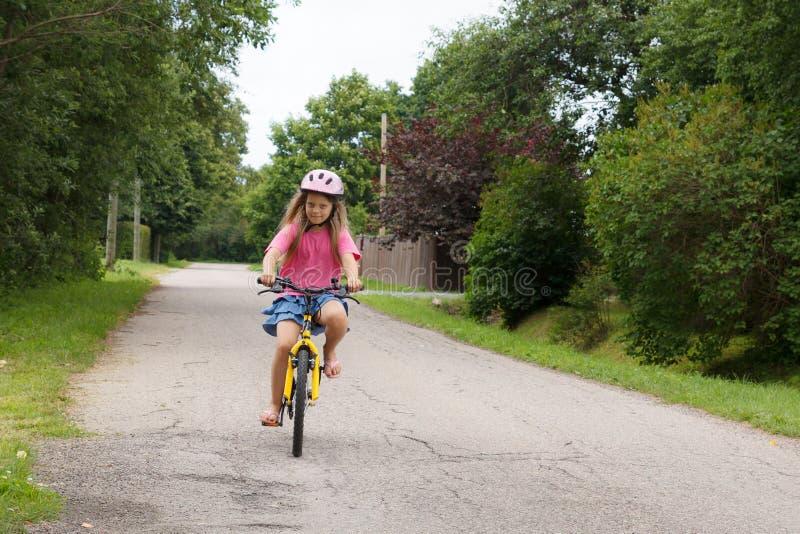 La muchacha monta una bicicleta fotografía de archivo