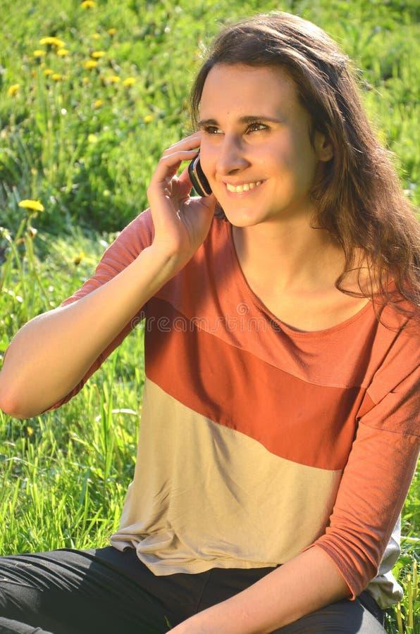 La muchacha morena atractiva hermosa se está sentando en un prado y está hablando en el teléfono móvil fotografía de archivo libre de regalías
