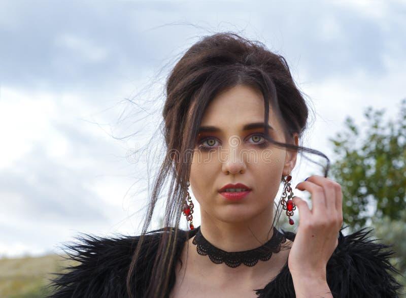 La muchacha morena atractiva hermosa se vistió en el estilo del vaquero del oeste salvaje que presentaba al aire libre fotos de archivo libres de regalías