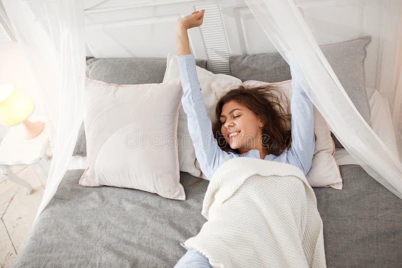 La muchacha morena bonita en el pijama azul claro está despertando en la cama del toldo debajo de la manta beige en la hoja gris fotografía de archivo