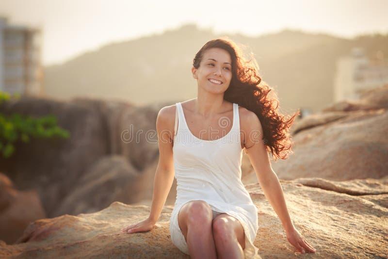 la muchacha morena bonita se sienta en piedra foto de archivo libre de regalías