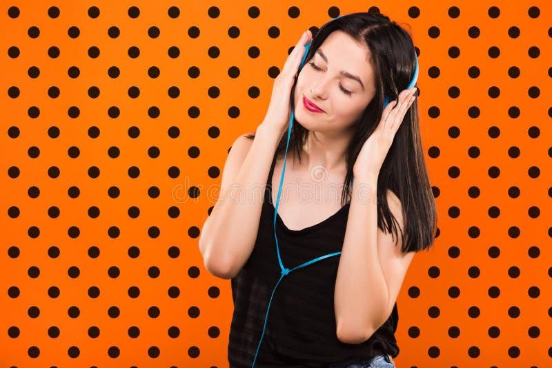 La muchacha morena con los auriculares en fondo anaranjado con negro hace fotografía de archivo libre de regalías