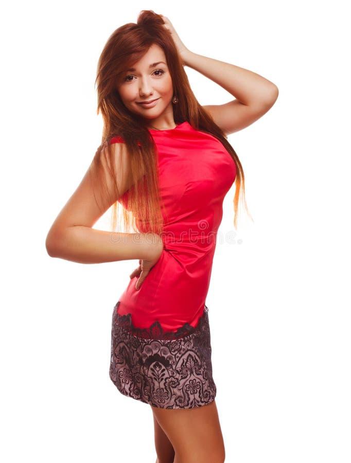 La muchacha morena de la mujer en vestido rojo corrige el pelo imagenes de archivo