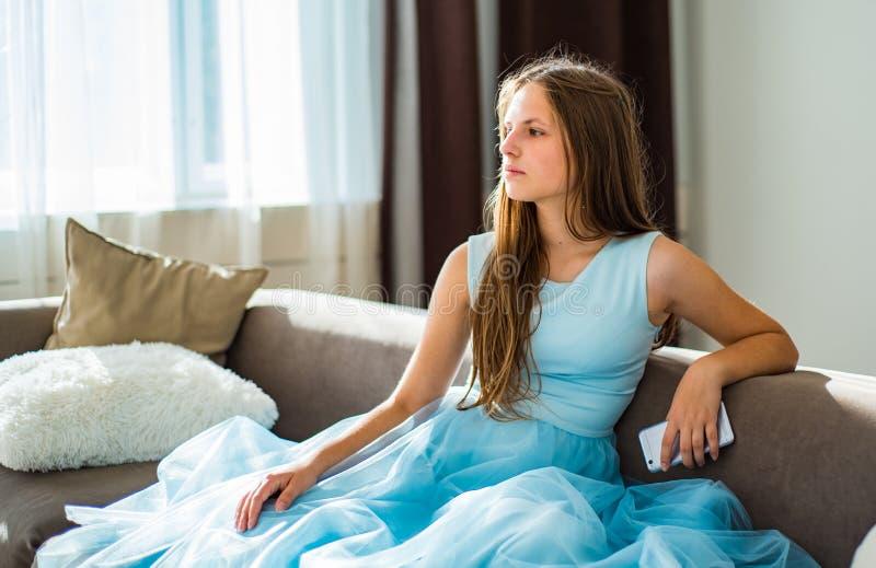 La muchacha morena del adolescente joven con el pelo largo que se sienta en el sofá en casa se divierte usando smartphone foto de archivo