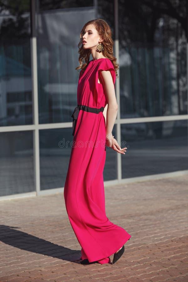 La muchacha morena elegante delgada vestida en guardapolvos fucsias del color está caminando en la calle de la ciudad en un día s foto de archivo libre de regalías