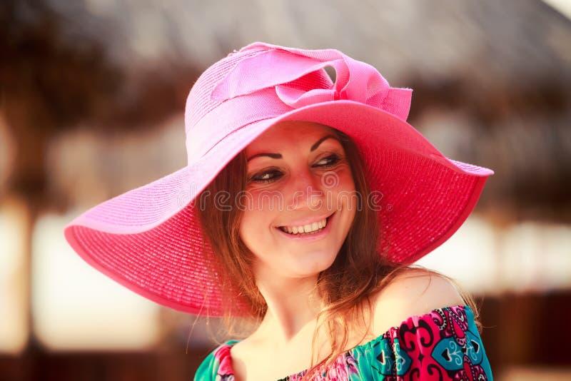 la muchacha morena en sonrisas rojas grandes del sombrero guiña en el paraguas defocused imagenes de archivo