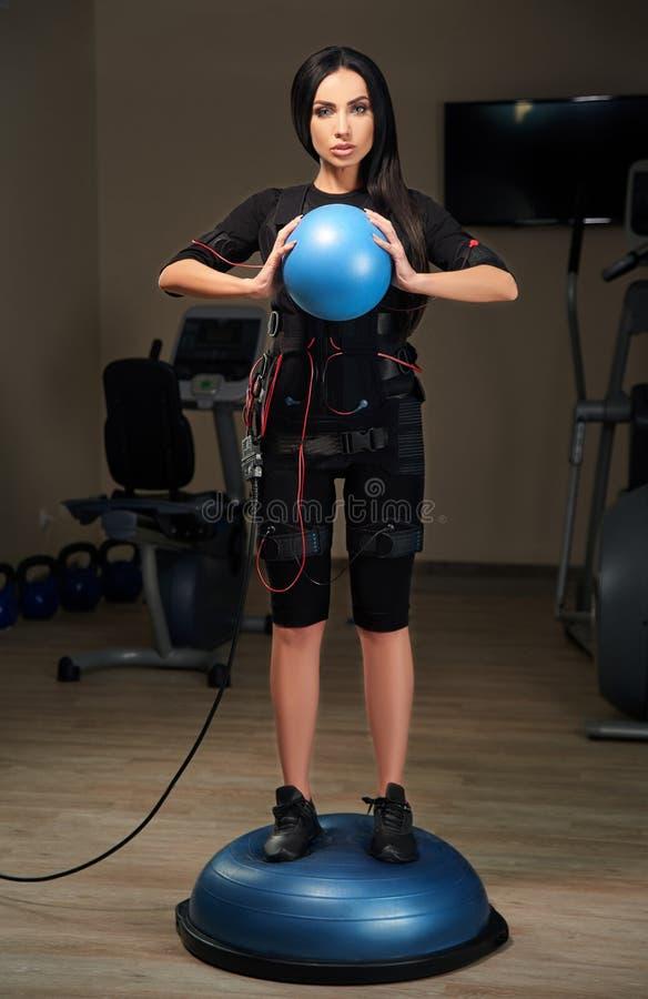 La muchacha morena en traje del ccsme se coloca en bola del bosu y el bal azul de los controles fotografía de archivo