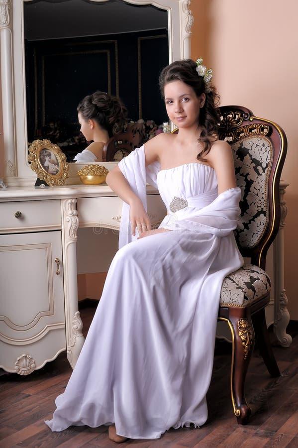 La muchacha morena en un vestido de noche blanco se sienta foto de archivo