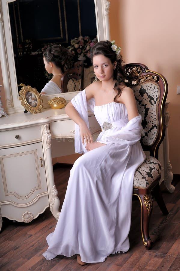 La muchacha morena en un vestido de noche blanco se sienta imágenes de archivo libres de regalías