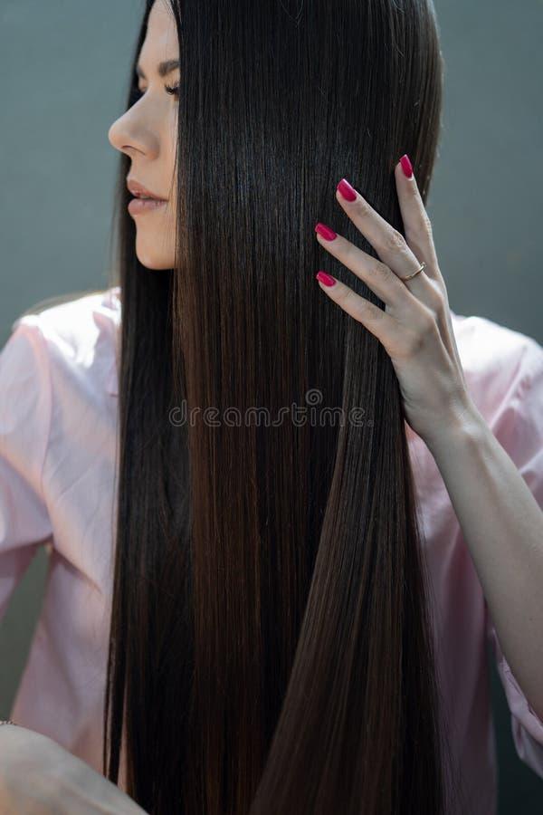 La muchacha morena en una camisa rosada está peinando su peine largo hermoso del pelo fotografía de archivo
