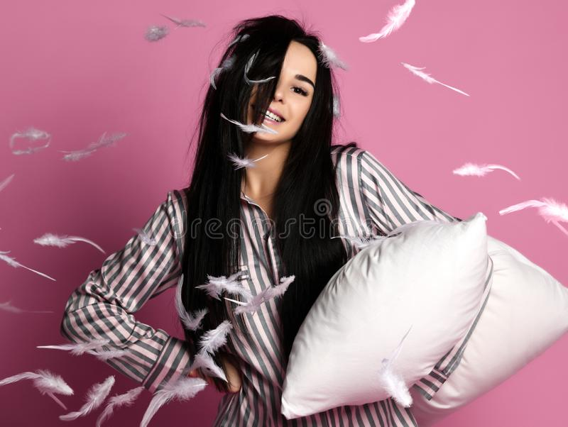 La muchacha morena hermosa acaba de despertar con la almohada y las plumas suaves Día soñoliento de bostezo de la mujer en rosa imagen de archivo libre de regalías